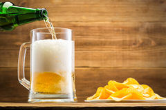Filling a glass with beer on the background of a wooden wall. Royalty Free Stock Images