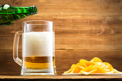 Filling a glass with beer on the background of a wooden wall. Royalty Free Stock Photo