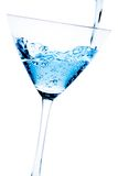 Filling a glass with blue cocktail tilted and bubbles Stock Photography