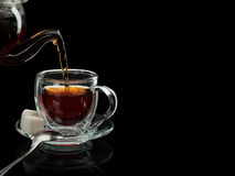 Filling of a glass cup by tea Royalty Free Stock Photography