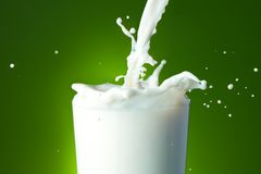 Filling the glass with milk. Close-up of a glass with milk that splashing on green background Stock Image