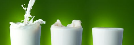 Filling the glass with milk. With splashes on green Stock Photography