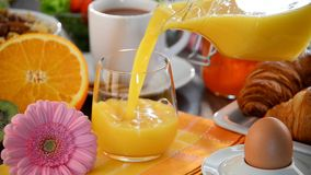 Filling glass with orange juice on table with breakfast stock footage