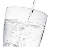 Filling a glass with pure water with bubbles and space for text. On white background Royalty Free Stock Photography