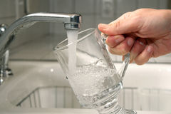 Filling a Glass with Water. A person fills a clear glass with water from the kitchen sink Stock Images