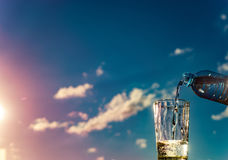 Filling of a glass by water against the sky. Filling a glass of water read with a palate royalty free stock image
