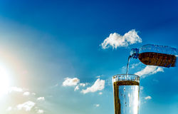 Filling of a glass by water against the sky. Filling a glass of water read with a palate stock images