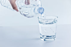 Filling a glass with water through bottle, nutrition and health-care concept Stock Images
