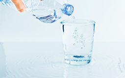 Filling a glass with water through bottle, nutrition and health-care concept Stock Photo
