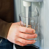 Filling Glass with Water from Dispenser Royalty Free Stock Photos