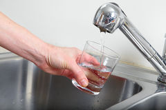 Filling glass of water Royalty Free Stock Image