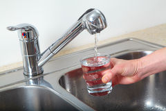 Filling glass of water Stock Images
