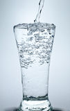 Filling a glass with water showing a drink concept. Filling a glass with water Stock Images