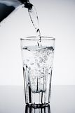 Filling a glass with water showing a drink concept. On table Stock Photography