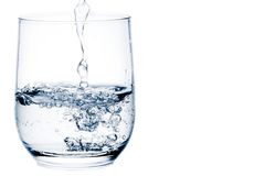 Filling a glass with water with space for text Royalty Free Stock Image