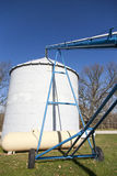 Filling a Grain Silo. A machine carries corn through the opening of a grain silo in Ohio Stock Image