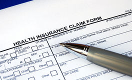 Filling the health insurance claim form. Isolated in blue Royalty Free Stock Photos