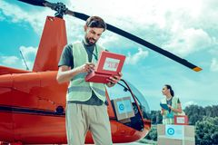 Attentive experienced bearded volunteer checking inside of first aid box royalty free stock photo