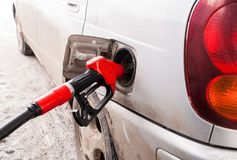 Filling hose with gasoline is inserting in fuel hole gray car. Royalty Free Stock Image