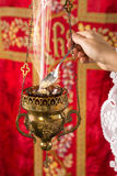 Filling incense holder. Hand adding incense chunks into a burning incense thurible Royalty Free Stock Image
