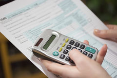 Filling income tax forms with calculator Royalty Free Stock Images