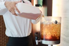 Filling the juice into a container with ice. royalty free stock image