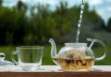 Filling the kettle with boiling water tea drinking on the verand Stock Image