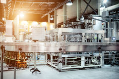 The filling machine pours beer into plastic PET bottles. Brewing production, abstract industrial background. Sunlight effect Royalty Free Stock Photography