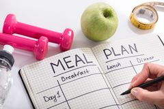 Filling Meal Plan In Notebook At Wooden Desk. High Angle View Of A Person Hand Filling Meal Plan In Notebook At Wooden Desk royalty free stock photos