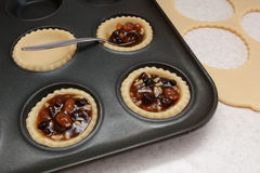 Filling mince pies with mincemeat Stock Photo