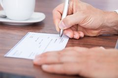 Filling out the amount on a cheque Royalty Free Stock Photos