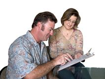 Filling Out Forms. A job applicant filling out forms with help from a woman - isolated royalty free stock photo