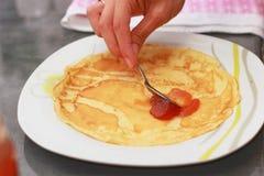 Filling pancake. Homemade jam on hot pancake stock image