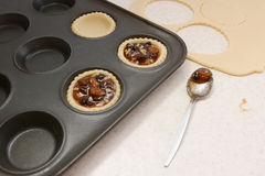 Filling pastry cases with mincemeat Royalty Free Stock Photos