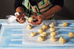 Filling puff pastries with cream using piping bag Royalty Free Stock Photos