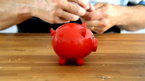 Filling red money pig Royalty Free Stock Images