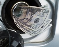 Filling the tank with $. A close up of an automotive gas filler being filled with money royalty free stock photos