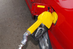 Filling the tank. Red car filling up at a gas station Stock Images