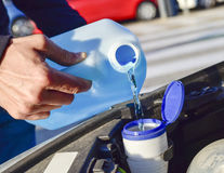Filling the tank of windshield washer fluid Royalty Free Stock Image