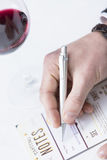Filling in a tasting sheet. Detail of a male hand is filling in a tasting sheet beside a glass of a red wine on a wine tasting session Stock Photos