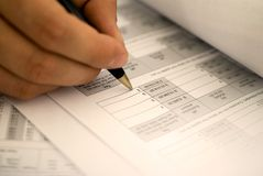 Filling in the tax form. Businessman filling in the annual tax form royalty free stock photo