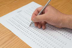 Filling test score sheet. With ballpoint Royalty Free Stock Photos