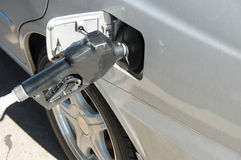 Filling up. Gas nozzle filling up car gas tank at gas/petrol station stock photography