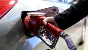 Filling up car gas tank with fuel at station. Closeup on hand and pump stock video footage