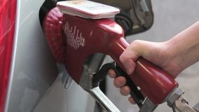 Filling up car gas tank with fuel at station. Closeup on hand and pump stock footage
