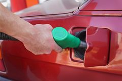 Power and energy fuel filling up. Filling up of  fuel at petrol station, closeup of workers hand Royalty Free Stock Image