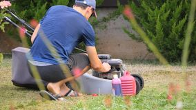 Filling up the lawn mower. A man is filling up the lawn mower outdoors stock footage