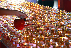 Filling up oil lamps on Wesak celebration Stock Images
