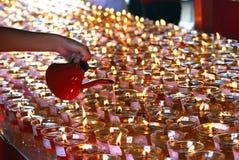 Filling up oil lamps on Wesak celebration Stock Images