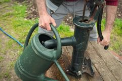Filling up the watering-can. Frontal landscape view of a farmer filling up the watering can at a pump well Royalty Free Stock Photography
